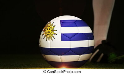 Football player kicking Uruguay flag ball - Football player...