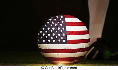 Football player kicking USA flag ball - Football player...