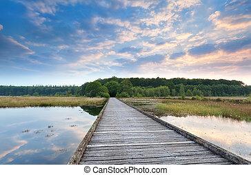 wooden bridge through swamp at sunrise