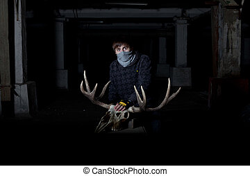 young man with a deer skull in front of him in a dark cellar