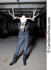 Man with a deer skull for a head in a dark basement
