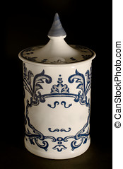 Antique ceramic canister on black background. Typical in European pharmacies