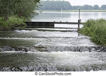 waterfall in holland from the river maas with green nature