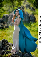 beautiful woman with blue cloak posing  outdoor