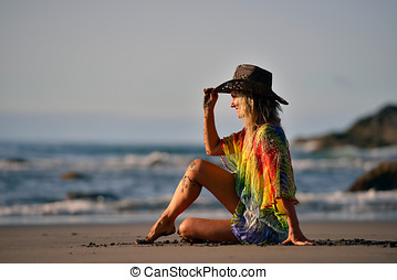 young beautiful woman sitting on the beach in summer