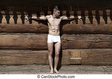 Young man shackled shadows wooden house - Sexy portrait of a...