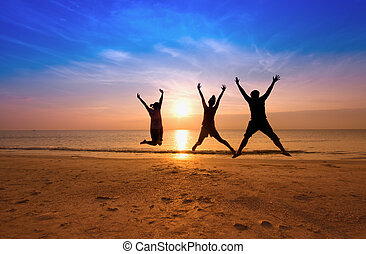 family jumping team on the beach on beautiful sunrise...