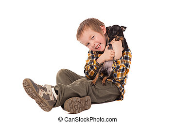 smiling little boy holding his puppy over white background