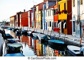 Venice, Burano island, boats on canal and colorful houses, Italy