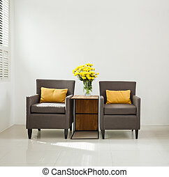 Grey sofa armchair in simple setting with yellow flowers