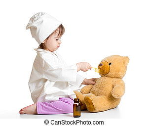 baby girl playing doctor and giving remedy to toy