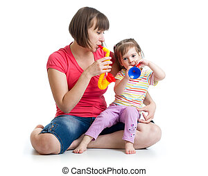 Mother and kid girl having fun with musical toys