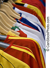 T-shirts stand - Image of colorful T-shirts on hangers in a...