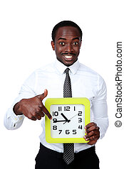 Time is money! Handsome african man holding a clock and...