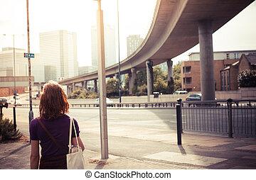 jovem, mulher, andar, à margem estrada
