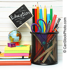 School-office stationery on book background