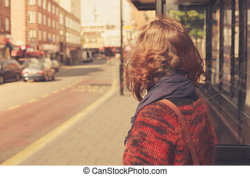Young woman at bust stop - A young woman is waiting at the...
