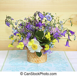 Lovely bouquet of wild wildflowers is in a vase near the wooden