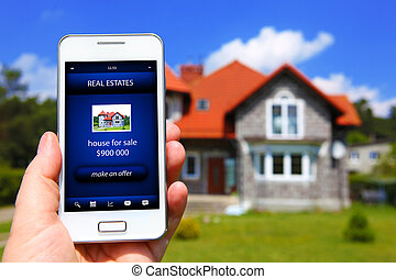 hand holding mobile phone with house sale offer and house as...