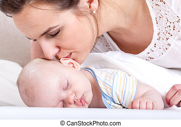 Mother kissing her baby - Horizontal view of mother kissing...