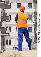Builder with spade looking at construction