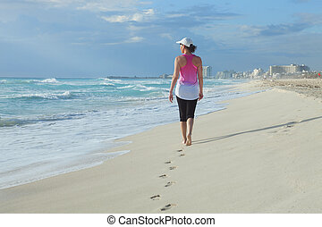 Woman walking on a Caribbean beach in the morning
