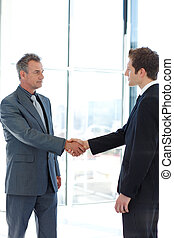 Senior and junior businessman shaking hands in agreement in...