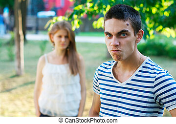 Angry young man with a girl at the background
