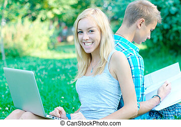Happy girl with a laptop and a student on the background at...