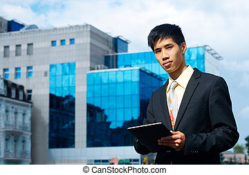 Young asian businessman with a tablet and business center on the background