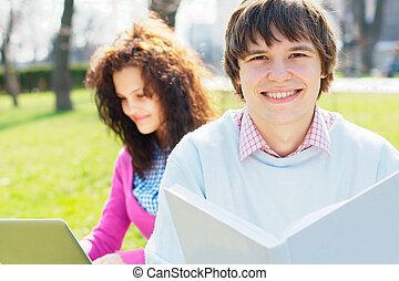Smiling student with a girl on the background at the park