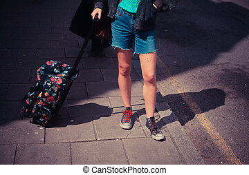 Young woman standing in the street with a suitcase