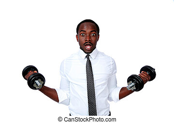 Portrait of a surprised african businessman lifting dumbbells on white background