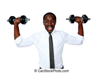Portrait of a laughing african businessman lifting dumbbells...