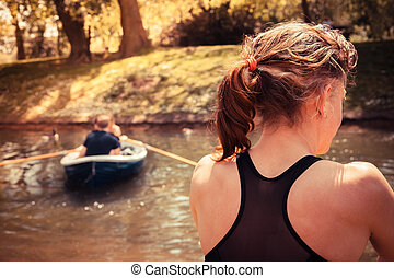 Woman relaxing by the water - A young woman is sitting on...