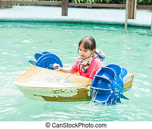 Young girl in a pedal boat - Young Asian girl pedalling a...