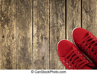 red sneakers on wooden deck - red sneakers in the right side...