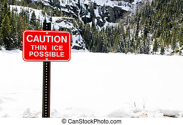 Danger thin ice sign on snowy lake - Thin ice sign next to...