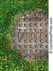 Sewer manhole with grass, Danger - Sewer manhole with the...