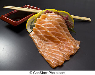 Salmon sushi sashimi over black background