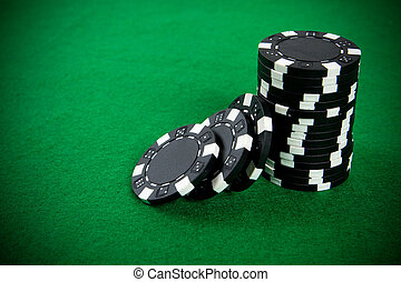 Stack of black poker chips on a green poker table...