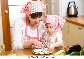 Young mother and her kid making funny vegetables dish