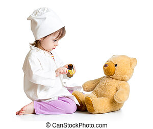 baby girl with clothes of doctor spoon feeding toy bear
