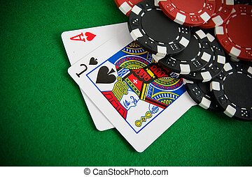 Ace of hearts and black jack with red and black poker chips...