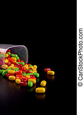 Colorful dragees on black wooden table surface.