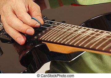 Rock guitarist playing the electric guitar closeup