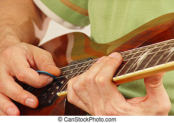 Hands of man playing the guitar closeup