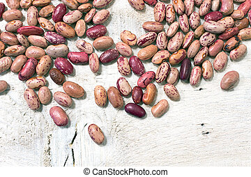Cranberry beans on white wooden background
