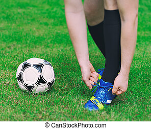 Football player tying his shoes on the field.
