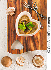 mushroom casserole in heart shape  with fresh parsley and cheese